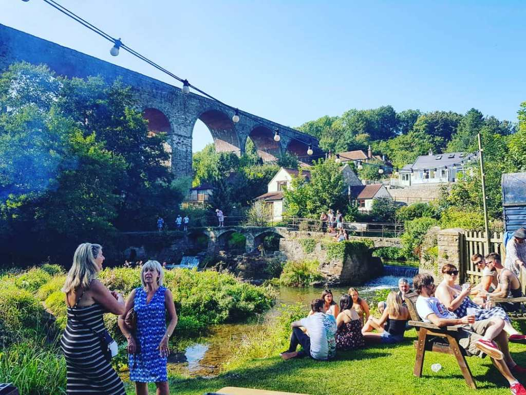 Pub garden with people and viaduct at The Rising Sun